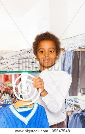 Positive African boy between rows with clothes