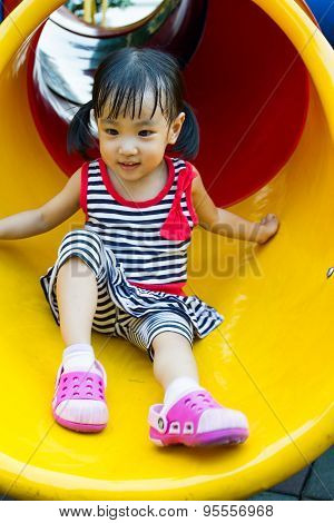 Asian Kid Sliding On Playground