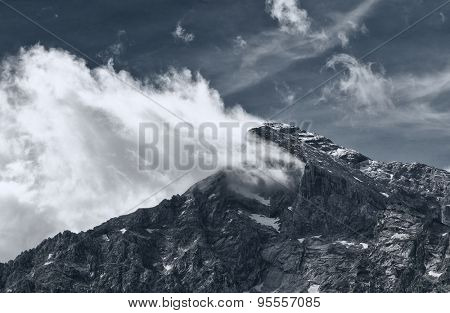 Black and white low angle view of rocky mountain peak with snow, partially obscured by cloud