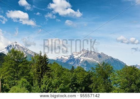 Snow-capped alpine peaks in the Berchtesgaden National Park, Bavaria, Germany in a scenic landscape under a cloudy blue sky