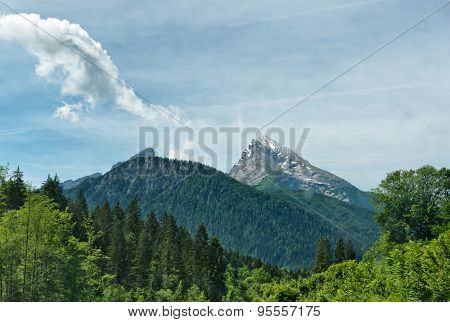 Vista of tree-covered mountains, snow capped top of mountain in background beneath cloudy blue sky