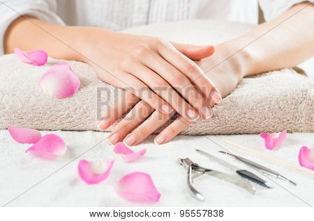 Closeup shot of female hands with french manicure on a towel surrounded by petals and manicure set. Woman getting nail manicure. Shallow depth of field with focus on woman hand.