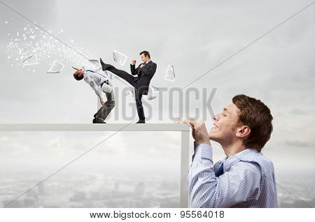 Young man looking from under table on two fighting colleagues