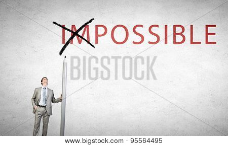 Young businessman with huge pencil changing word impossible