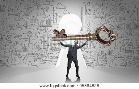 Young businessman and keyhole at background lifting big key above head