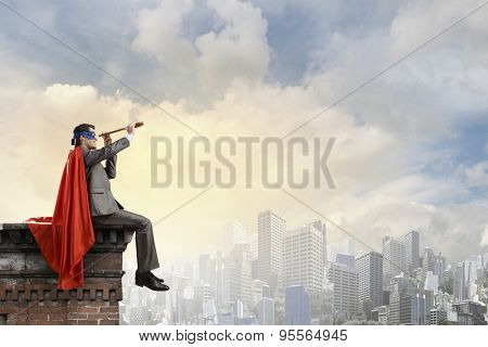 Super hero sitting on top of building and looking in spyglass