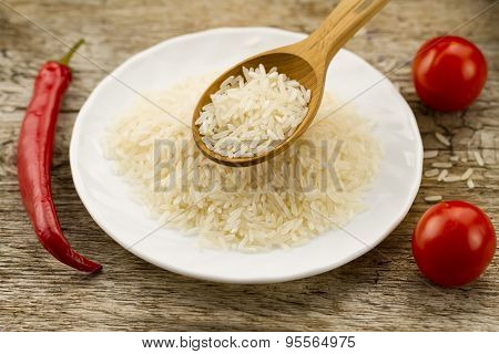 Long Grain Rice In A Wooden Spoon On A Background Plates, Chili Pepper, Cherry Tomato. Healthy Eatin