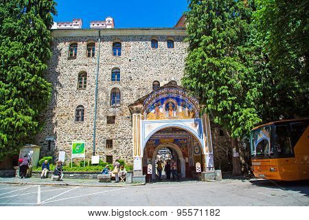 Tourists Near The Entrance Arch Of Famous Rila Monastery, Bulgaria