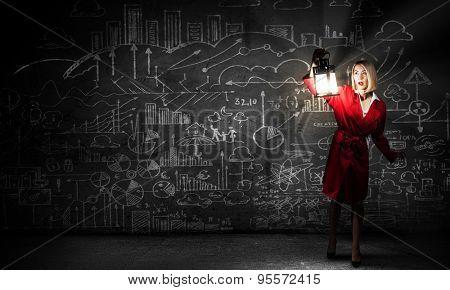 Young woman in red coat with lantern lost in darkness