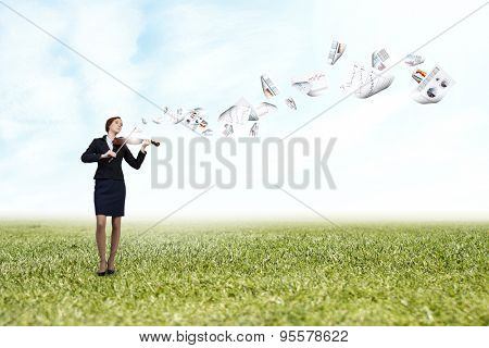Young pretty businesswoman playing violin and papers flying in air