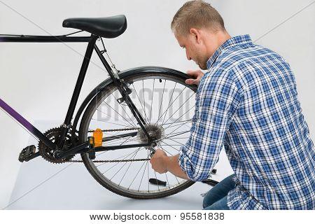 Young Man Repairing Bike