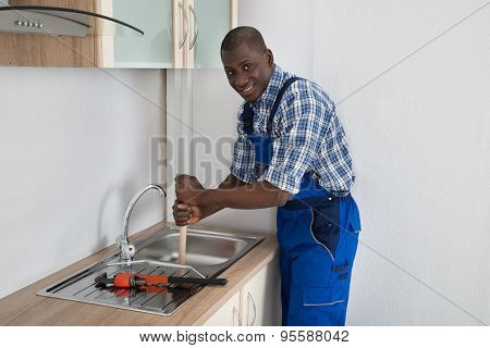 Plumber Using Plunger In Kitchen Sink