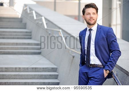 Nice businessman leaning on handrail