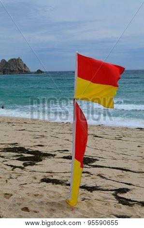 Lifeguard flags on sandy beach.