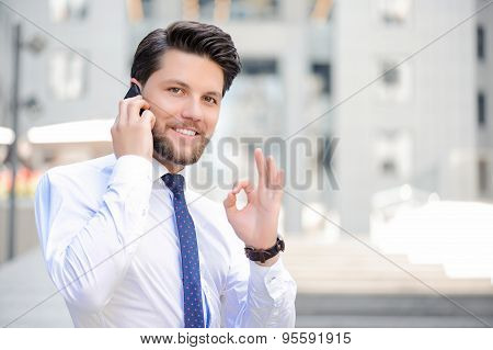 Nice young businessman holding mobile phone