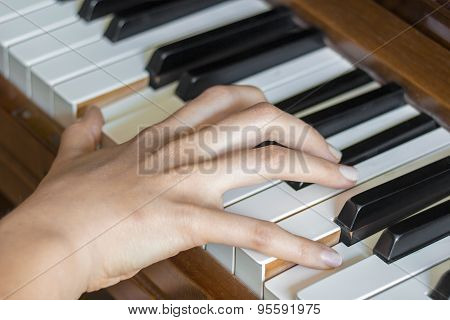 Girl's Right Hand Finger Holding Pressed  Keys On A Piano