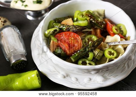 Roasted asparagus and tasty colorful pasta with vegetables, spices in bowl on colorful background
