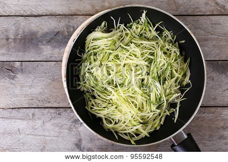 Grated zucchini and squash in pan on wooden table close up