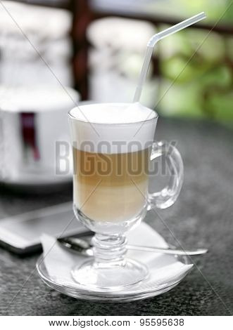 Glass of latte on table in cafe close-up