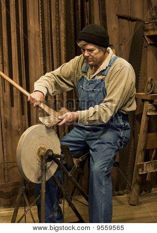 Mann schärfen einer Axt auf einem Schleif-Stein
