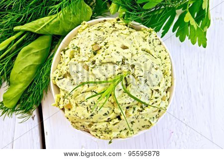 Butter with spinach and herbs in bowl on light board