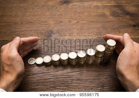 Businessman's Hand Protecting Coins On Desk