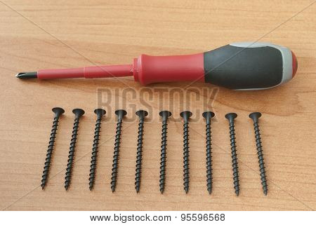 Screwdriver And Screws Are On A Wooden Board