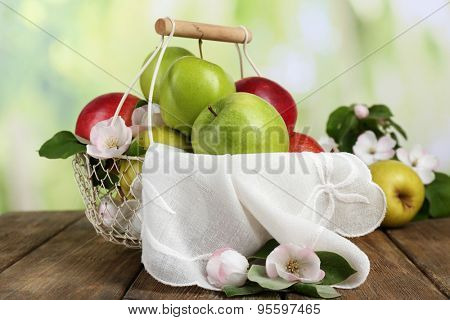 Fresh apples with apple blossom in basket, on wooden table, on nature background