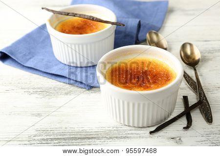 Creme brulee dessert  on napkin, on color wooden background
