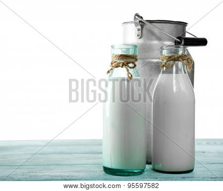 Retro can for milk and glass bottles of milk on wooden table, on white background