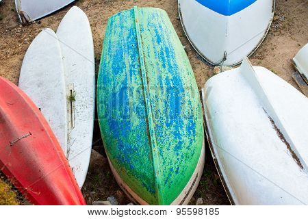 Old small boats on sandy beach close up. Weathered and dirty dinghies scattered across the sand