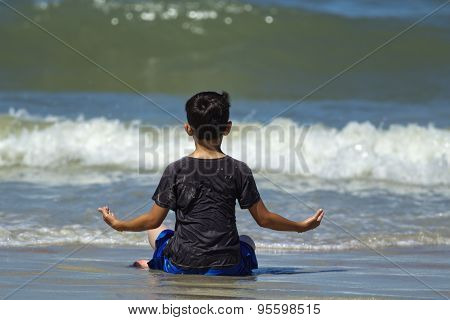 Boy Meditates On The Beach.