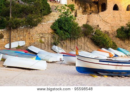 Many old small boats on sandy beach. Weathered and dirty dinghies scattered across the sand