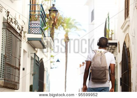 Young Black Man Waking In Town With Bag