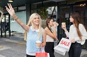 foto of cabs  - young happy girl calling for taxi cab along city sidewalk with coffee cup sale shopping bag friends - JPG