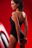 pic of handcuff  - Beautiful brunette woman in handcuffs on a red background - JPG