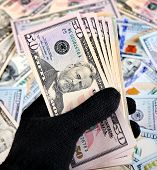 stock photo of american money  - Money in the Hand in the Black Glove on American Dollars Background - JPG