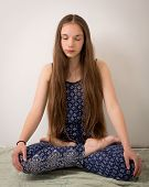picture of hippy  - Beautiful teenage hippie brunette girl with extremely long hair sitting in a lotus pose and eyes closed - JPG