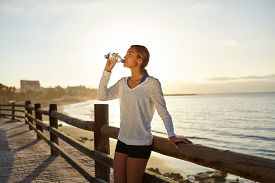 stock photo of jogger  - Young jogger drinking an energy drink outdoors in summertime with back lit - JPG