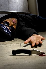 picture of gang  - young black male murdered in a street alley with a bloody knife.  the man is a victim of gang violence