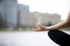 image of pranayama  - Close up of hands of young office yogi woman sitting cross legged in yoga Easy Sukhasana Pose on riverbank in the city meditating with fingers in Jnana mudra - JPG
