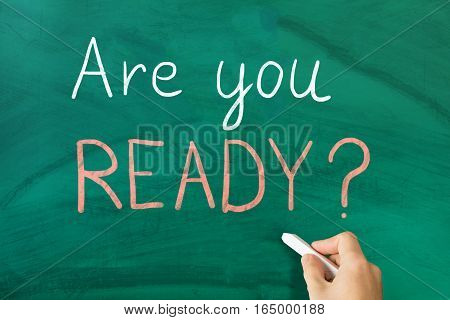 Close-up Of Person Handwritten Are You Ready Text On Notepad At Wooden Desk