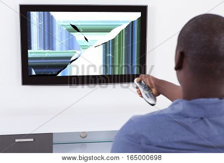 African Man With Remote Control In Front Of Television Showing Distorted Screen