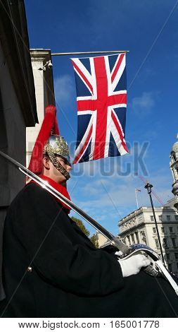 LONDON, UK - OCTOBER 20, 2016: Queen's horse guard on duty with his sword under the British flag in London