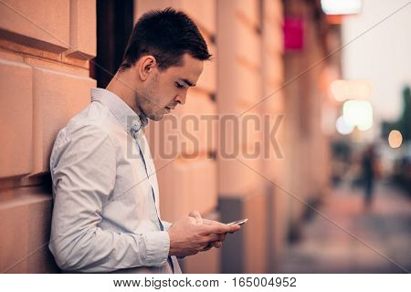 Casually dressed handsome young man leaning on a wall on a city street sending text messages on his cellphone