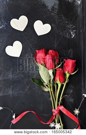 Top view of beautiful long stem roses for Valentines Day tied with a red ribbon with fairy lights and wooden heart shaped cutouts.