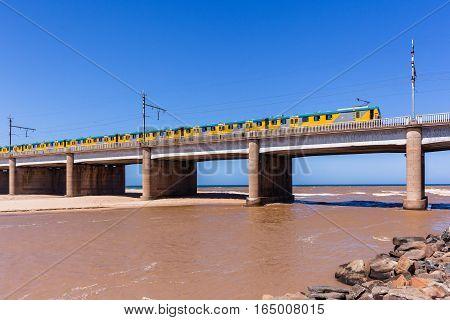 Train bridge beach coastline crossing river flooding brown water into ocean