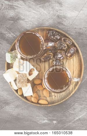 Black Tea, Oriental Sweets, Dates And Nuts On A Dark Background. Top View. Food Background. Toning
