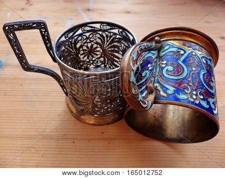 Two cupholders. Cupholder appeared on the Russian railway in 1892. Cupronickel, tracery pattern, coloured enamel, oriental pattern. Closeup. Retro.