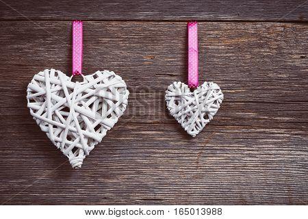 Wicker heart on the board. Wood background